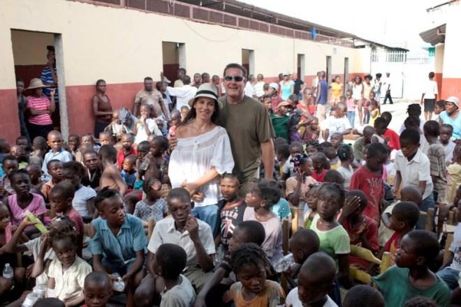 Paola Turci in compagnia di Padre Rick e dei bambini haitiani durante uno dei suoi viaggi sull'isola.